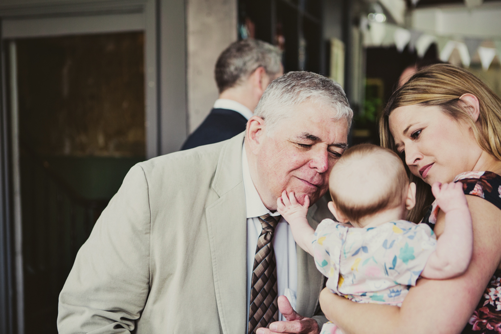 grandpa and baby at a wedding reception in Hackney