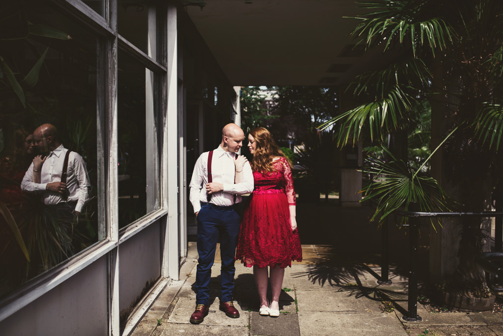 Red vintage bride with groom wearing red braces London wedding elopement