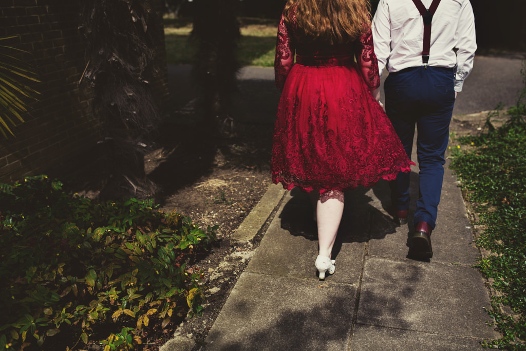 Bride wearing vintage red lace bridal dress walking with groom for London wedding elopement