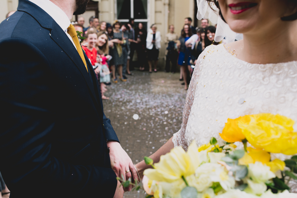 bride and groom holding hands after confetti throw outside Brighton Town Hall Wedding