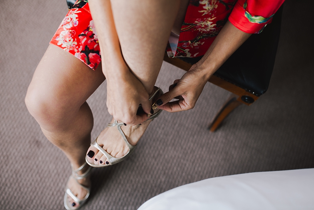 bride putting her shoes on the morning of her Wiltons Music Hall Wedding