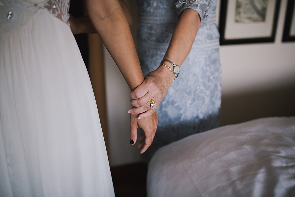 mum holding brides hand the morning of her wedding