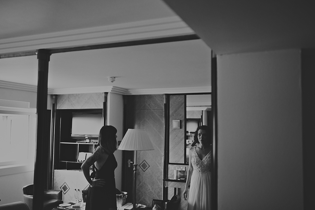 Bride checking her wedding dress in the mirror before leaving for the wedding ceremony