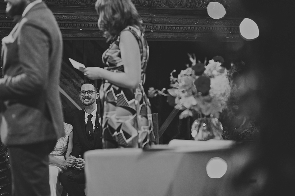 groom smiling during a a reading at a wedding ceremony at Wiltons Music Hall