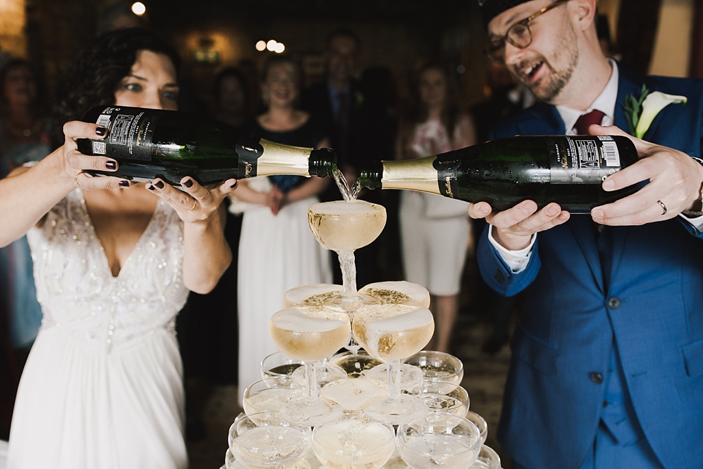 Couple pouring champagne for the champagne tower at their Wiltons Music Hall Wedding