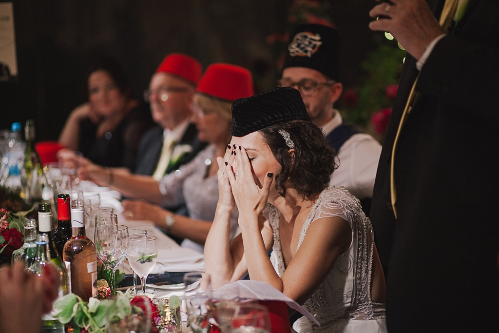 bride holding her head as dad embarrass' her during father of the bride speech