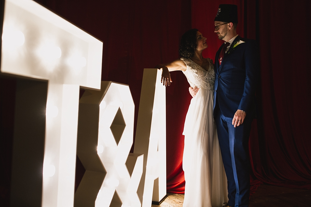 bride & groom stood next to their initials in giant light up letters