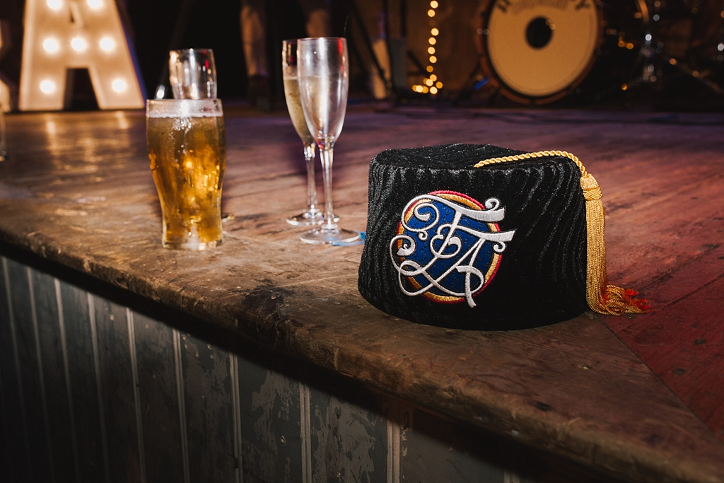custome made fez and a pint of beer on stage at a Wiltons Music Hall Wedding