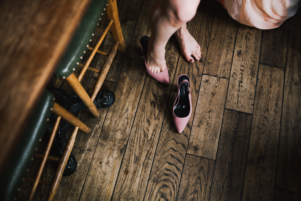 Bride putting on shoes at London pub wedding | Lisa Jane Photography | Modern London Pub Wedding Photography