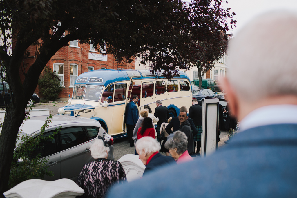 Guests getting on vintage wedding bus at Southend wedding | Lisa Jane Photography | Creative London Wedding Photography