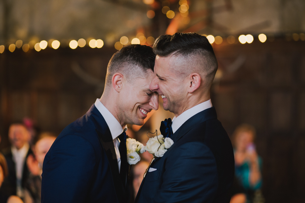 Two grooms laughing during a weddin ceremony at Battersea Arts Centre | Lisa Jane Photography | Modern London Wedding Photography