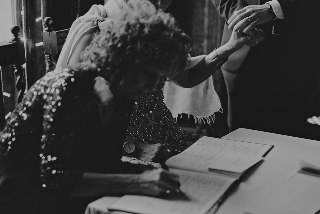 Holding hands during signing of the regisiter at a Battersea Arts Centre wedding | Lisa Jane Photography | Modern London Wedding Photography