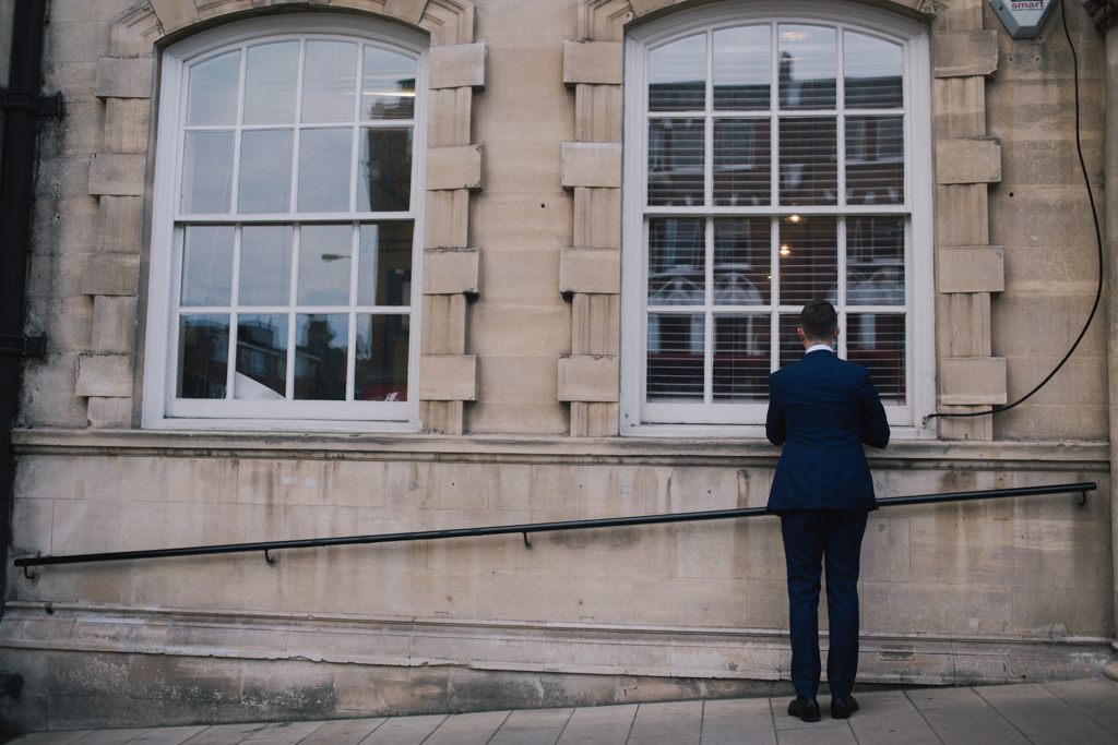 Groom checking himself in the window before his group shot at a Battersea Arts Centre wedding | Lisa Jane Photography | Modern London Wedding Photography