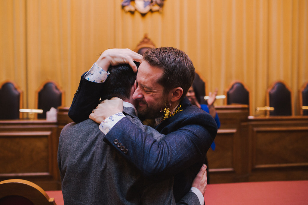 Two grooms hugging at Wandsworth Town Hall wedding