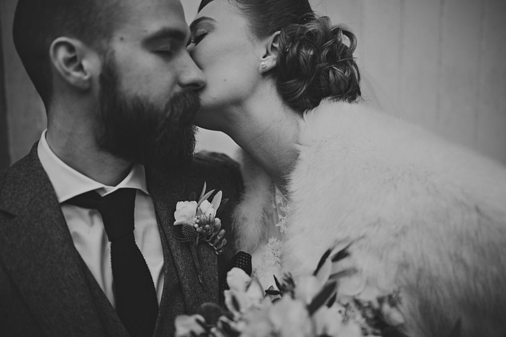bride kissing groom at Northbrook Park wedding bride