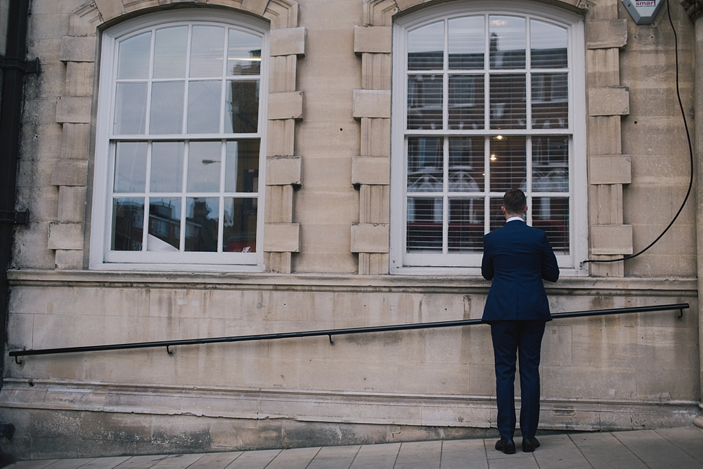 Groom checking himself in window before the wedding ceremony at Battersea Arts Centre by Lisa Jane Photography