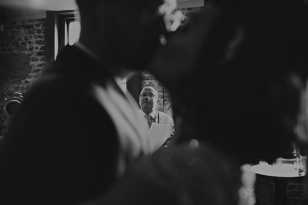 couple kissing while dad plays guitar during their wedding reception at Wiltons Music Hall