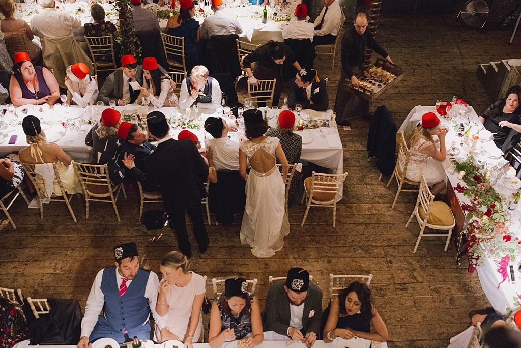 Bride and groom chatting to guests during dinner at Wiltons music hall