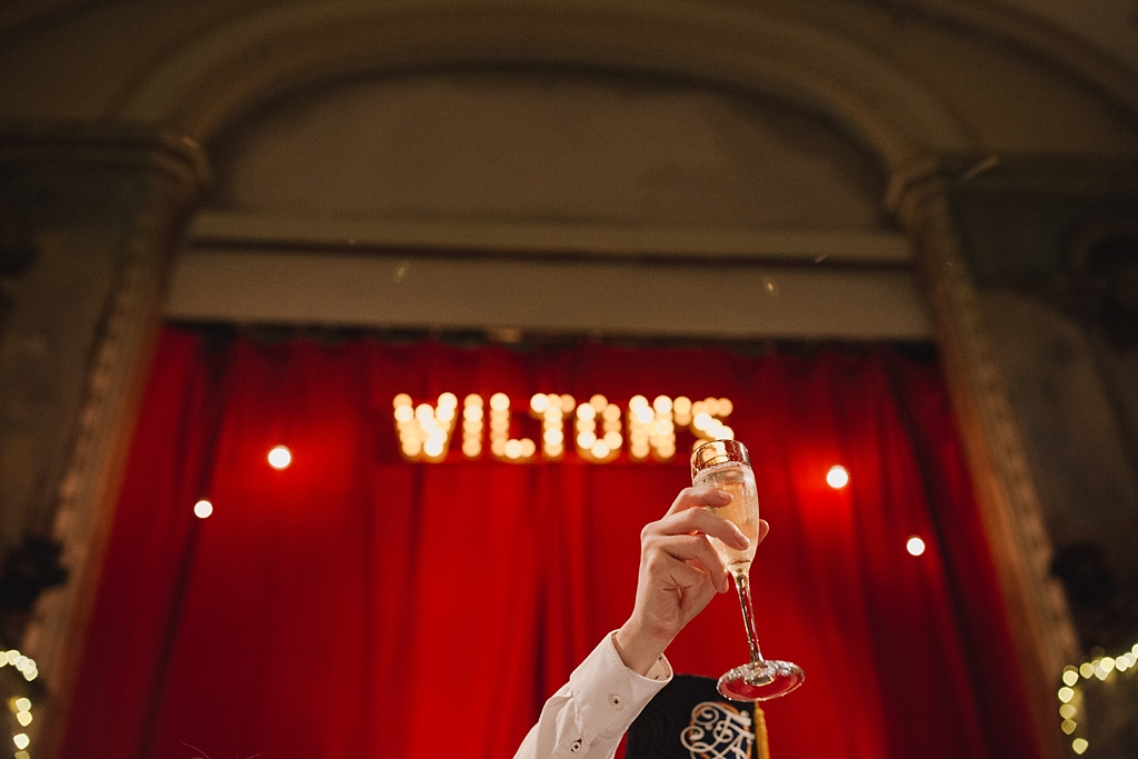 groom holding a glass of champagne during a toast at Wiltons Music Hall