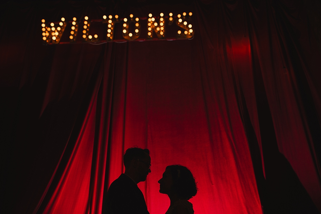 Bride & groom silhouetted against the stage curtains   Wiltons Music Hall Wedding Photographer   Lisa Jane Photography